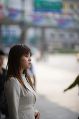 Young adult business woman walking through the street.