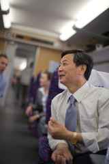 Mature businessman sitting on a train.