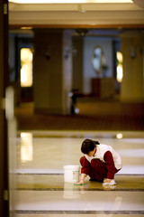 Mid-adult woman cleaning the floor in a lobby.