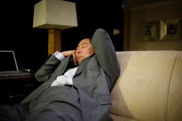 Mid-adult businessman sleeping on a couch in an office.