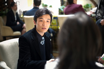 Young adult businessman sitting with colleagues in a cafe.