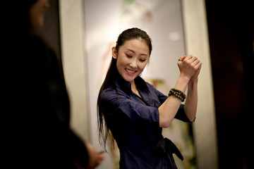 Young adult business woman dancing in an office.