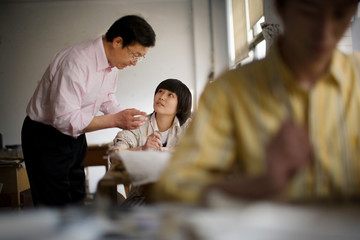 Mid-adult man teaching a student in a classroom.