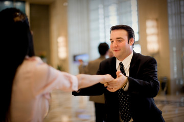 Young adult couple dancing in a lobby.