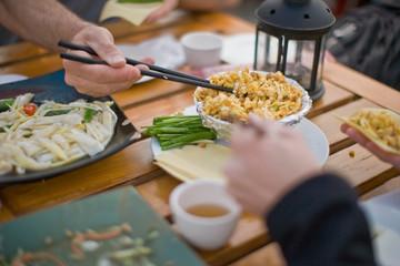 Chopsticks picking up food on a restaurant table.