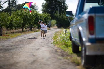 Two young boys running and flying a kite in an orchard
