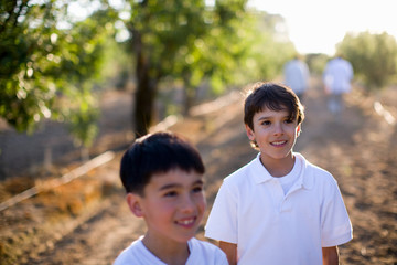 Two young boys standing in an orchard looking happy