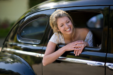 Young adult bride with her head out the window of a car on her wedding day.