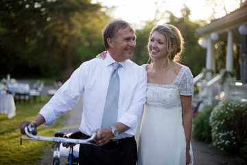 Smiling bride and groom with bicycle walking outdoors