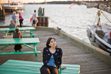 Mid-adult woman looking upwards while sitting on a wooden picnic table on a busy wooden wharf.