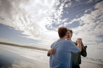 Homosexual male couple dancing together on a beach.