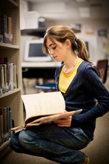 Teenage girl looking at books in a school library.