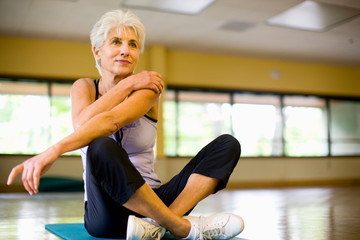 Mature adult woman stretching her shoulder at a gym.