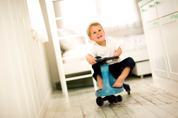 Boy riding on toy car in house