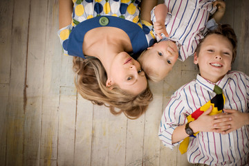 Portrait of a young adult woman with her young son and toddler lying on the floor.