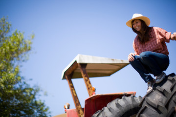 Woman crouching on tractor tire
