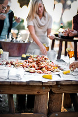 People standing around a table of fresh seafood at an outdoor dinner party
