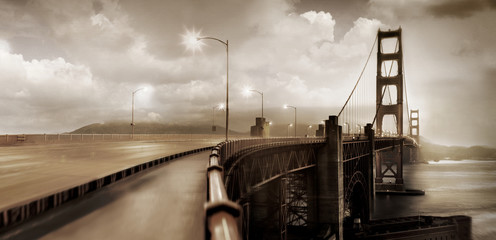 Suspension bridge underneath moody sky.