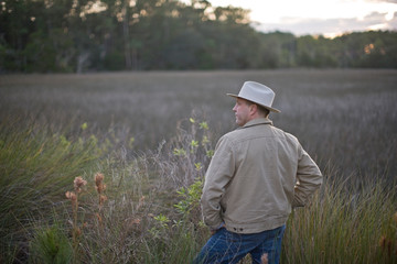Man wearing a fedora hat and standing in a field