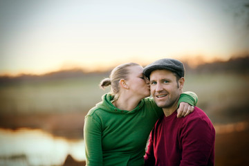 Portrait of a young adult man being kissed on the cheek by his wife while near a lake.