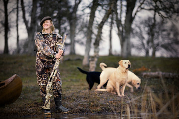 Young adult woman duck shooting with her dogs by a lake.