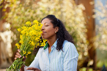 Happy mid adult woman smelling a bunch of flowers outdoors.