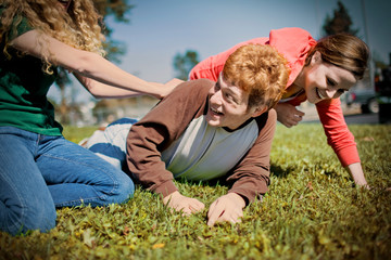 Laughing teenage boy playing with his two female friends on a grassy lawn in the sun.