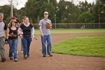 Friends walking across sport field