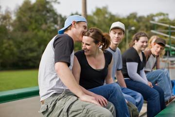 Friends sitting on bleachers at sport field