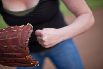 Woman standing on sport field with baseball mitt