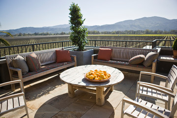 Plate of oranges on a table surrounded by chairs on an outdoor patio.