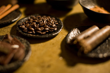 Small dish full of fresh brown coffee beans surrounded by other spices.