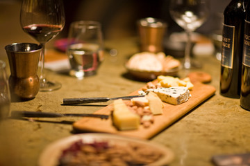 Cheeseboard and wine glasses on a rustic table.