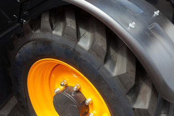 Close up side view photo of fragment huge tire wheel of construction or agriculture automotive equipment