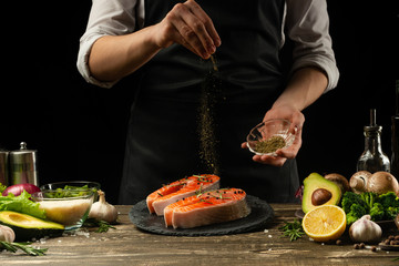 The chef prepares fresh salmon fish, fresh salmon, sprinkles with spices and Provencal herbs with ingredients.Frost in the air. cooking fish food.Cooking vegan cuisine, restaurants,hotel business