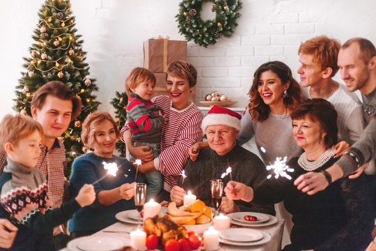 Happy big family at Christmas dinner. Children are happy new year holding sparklers in their hands