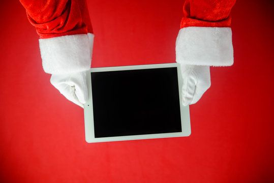 Santa showing tablet PC during holiday time, mockup electronic communications technology equipment background. Closeup image of hands working with video or photography on smart pad.