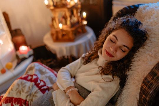 Hübsche junge Frau schläft friedlich auf einem Sessel mit festlichen Lichtern im Hintergrund