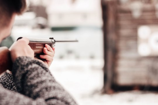 man shoots at a target from an air rifle in the winter. shooting range