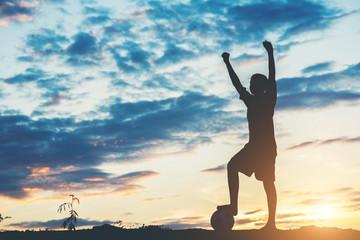 Silhouette of children play soccer football