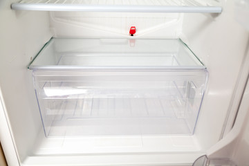transparent box stands bottom of  empty refrigerator