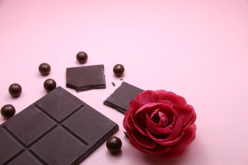 Pieces of dark chocolate bar and milk chocolate pearls and valentines rose on pink background, top view, copy space