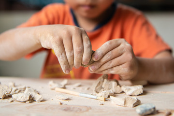 Kid playing with educational archaeology toy