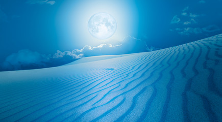 """Night sky with blue moon in the clouds with desert (sand dune)""""Elements of this image furnished by NASA"""
