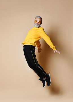 Excited senior millionaire man dancing jumping in yellow sunglasses hands up fashionable men senior