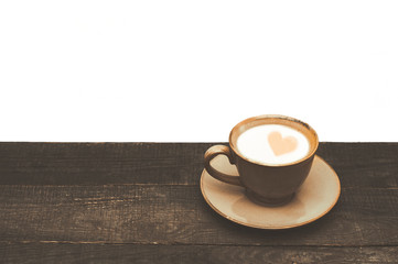 Cup of coffee with milk on a wooden table. White background. A heart