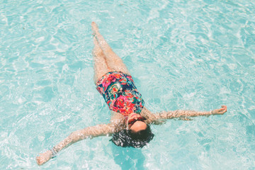 A pregnant woman floating in a swimming pool in summer.