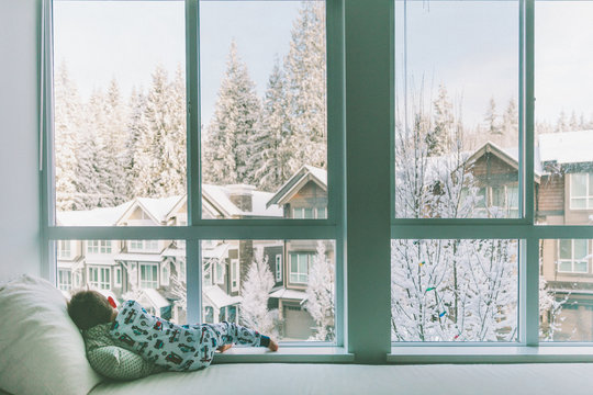 A child looking out the window on a beautiful snowy day.