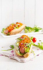 Hot dog with  cucumber, carrot, tomato and lettuce on wooden background. Fast food menu.