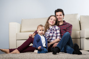 Family with a baby in a room with a sofa